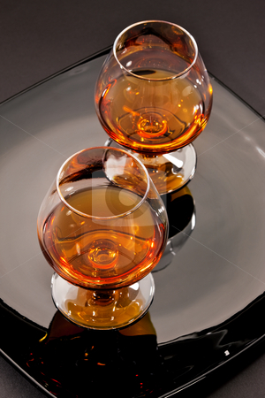Cognac stock photo, Drink series: two glass of cognac on the black plate by Gennady Kravetsky
