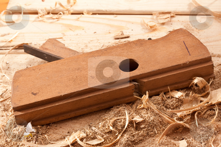 Plane stock photo, Tools series: steel plane on wooden plank with shaving by Gennady Kravetsky
