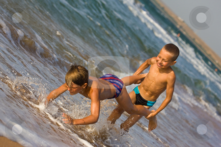 Two boy stock photo, People series: two boy are play the game on sea beach by Gennady Kravetsky
