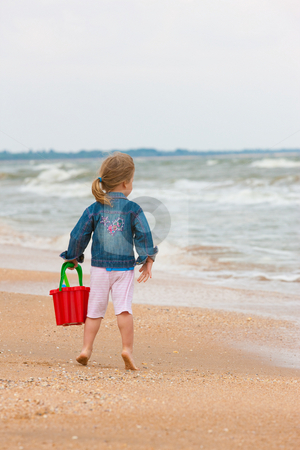 Recreation on the beach stock photo, People series: little girl on the beach play with toy by Gennady Kravetsky
