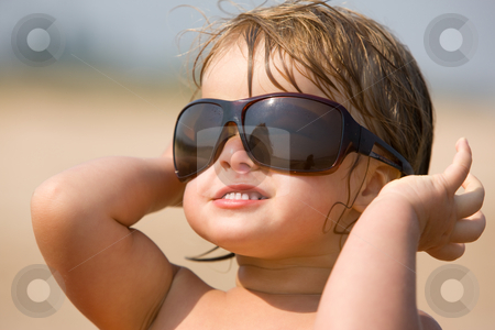 Childhood stock photo, Little girl are play with the sun glasses by Gennady Kravetsky