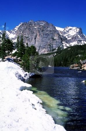Mountain Lake stock photo, Snow surrounds a clear mountain lake in early spring. by Trenton Thomas