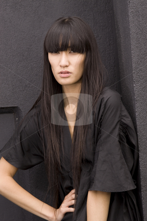 Young female model in black stock photo, Young asian female in a black dress against a black background by Jandrie Lombard