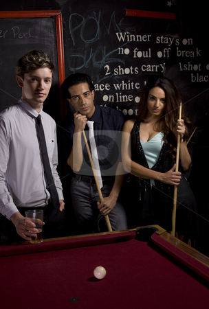 Playing Pool stock photo, Three young people playing a game of pool in a pub by Jandrie Lombard