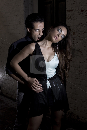 Forbidden love stock photo, Vampire getting ready to bite a girl on the neck by Jandrie Lombard