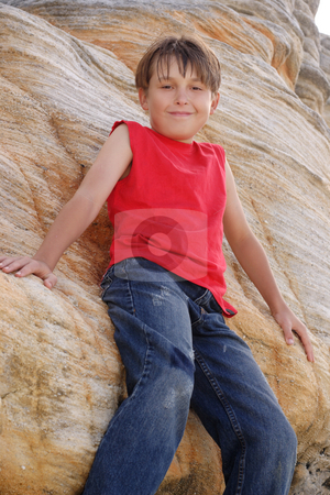 Child standing by a rockface stock photo, Smiling young child leaning against a tall sandstone cliff face by Leah-Anne Thompson