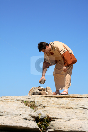 Man picking up rock or making rock pile. stock photo, Full length man in brown and beige  tunic robe bending over near a pile of rocks.  Concept sin, law or culture.  This form of punishment was used in many ancient cultures and is still used in some cultures today.   Space for a heading, title or verse. by Leah-Anne Thompson