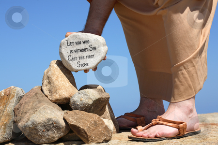 Man holding rock with bible verse  stock photo, A man holds a white rock inscribed with a bible verse from John    Closeup.  Focus to rock. by Leah-Anne Thompson