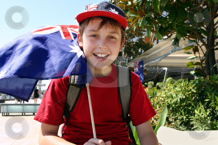 Joyful child flying flag stock photo, Happy patriotic young boy flying a flag on summer national day. by Leah-Anne Thompson