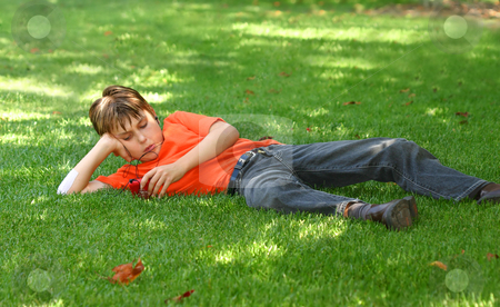 Boy in park listening to mp3 player stock photo, A young boy sprawled out on the shaded grass in the park, listens to music on an mp3 music player. by Leah-Anne Thompson