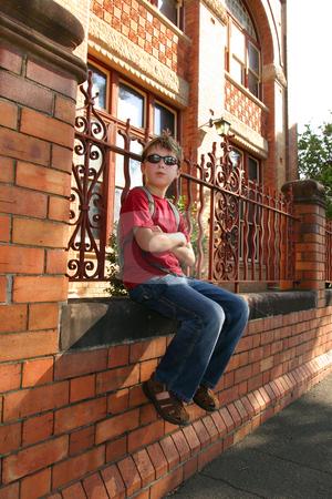 Child sitting on brick wall stock photo, Child sitting on brick wall outside a school building. by Leah-Anne Thompson
