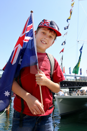 Aussie boy harbourside stock photo, Young aussie boy proudly holding flag by the harbourside mariner on Australia Day national holiday. by Leah-Anne Thompson