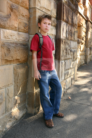 Youth leaning against sandstone wall stock photo, Trendy boy in denim jeans and t-shirt leaning against a standstone brick wall.