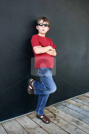 Child leaning against dark wall stock photo, Child in jeans and t-shirt stands casually leaning partially against the wall behind him. Added contast. by Leah-Anne Thompson