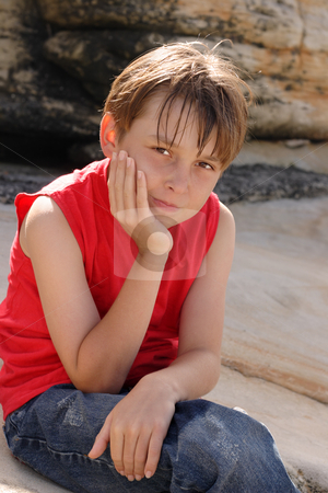 Child sitting on rocks stock photo, A young child dressed in jeans and tank top sitting and thinking by rocks. by Leah-Anne Thompson