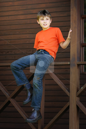 Boy sitting on the verandah stock photo, A child sits on the timber balustrade of a verandah - 400 iso by Leah-Anne Thompson