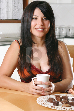 Woman relaxing with coffee stock photo, A pretty woman sitting down at a table with a cup of coffee. by Leah-Anne Thompson