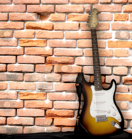 Guitar leaning on a wall stock photo, Electric guitar leaning over a brick wall by Fabio Alcini