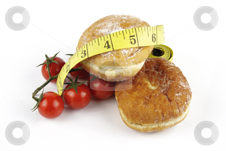 Tomatoes and Doughnuts with Tape Measure stock photo, Contradiction between healthy food and junk food using red ripe tomatoes and doughnuts with a yellow tape measure on a reflective white background by Keith Wilson