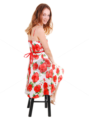 Pretty girl in colorful dress. stock photo, Young, lovely girl in a colorful dress with brown hair, looking  over her shoulder,  in high heels sitting on a bar chair, in the studio for white background. by Horst Petzold