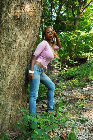 Girl in the woods. stock photo, An Jamaican woman in jeans and pink sweater leaning on a big tree in the woods, in nice sunshine. by Horst Petzold