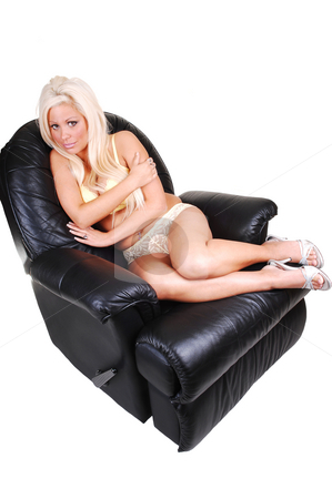 Girl in lingerie. stock photo, A beautiful girl with long white blond hair sitting in a black leather chair in yellow lingerie, looking up to the camera with beautiful eyes. by Horst Petzold
