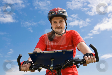Cyclist on the mountain bike stock photo, Portrait of adult cyclist on the mountain bike against blue sky by Tatsiana Amelina
