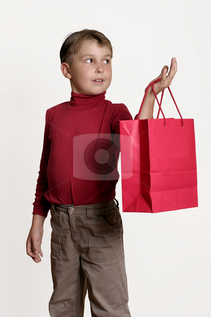 Child with a red gift bag stock photo, Child holding a red gift bag in one hand and looking off to the side. by Leah-Anne Thompson