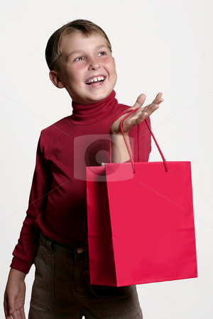 Gift Shopping stock photo, Joyous young boy with a red shopping bag by Leah-Anne Thompson