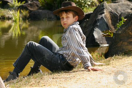 Rural boy sitting by banks of a river stock photo, Young rural boy sitting on the banks of a small river inlet in outback Australia. by Leah-Anne Thompson