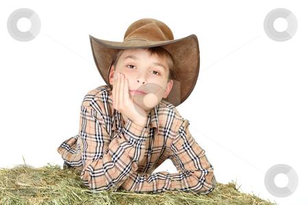 Farm boy leaning on lucerne bale stock photo, A country farm boy leaning on a bale of lucerne hay. by Leah-Anne Thompson
