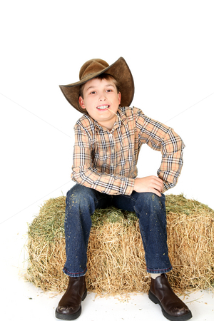 Boy chewing on a piece of straw stock photo, A boy sitting casually chews on a piece of lucerne hay. by Leah-Anne Thompson