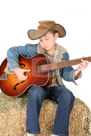 Playing guitar stock photo, A child strums an acoustic guitar by Leah-Anne Thompson
