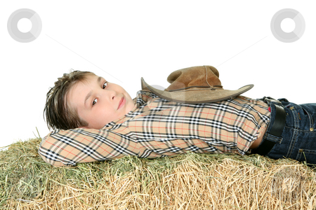 Country boy resting on hay stock photo, Country boy in checked shirt and jeans rests on a bale of lucern hay. by Leah-Anne Thompson