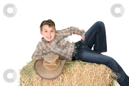 Rural child lying on hay bale stock photo, A boy from the country lays casually on a hay bale and smiles.  White background. by Leah-Anne Thompson