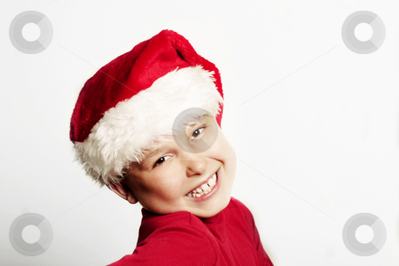 Cheerful child wearing a red Christmas hat stock photo, Seasonal Joy and happiness. by Leah-Anne Thompson