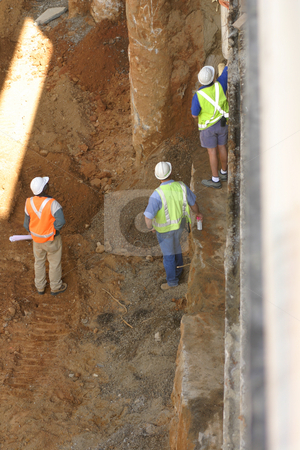 Construction workers stock photo, Three construction workers, one holding blueprints, on an excavation site by Leah-Anne Thompson