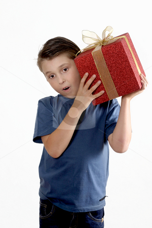 Child shaking a wrapped present stock photo, A young boy wearing jeans and t-shirt shakes a present to determine the contents. by Leah-Anne Thompson