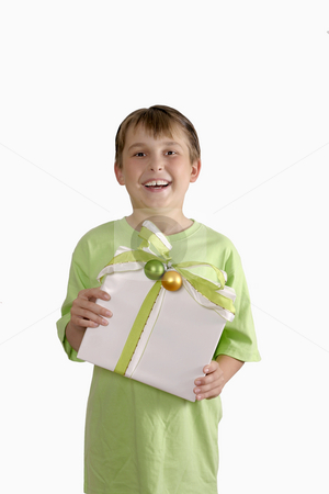 Smiling boy holding a gift stock photo, Smiling child holding a pretty wrapped gift by Leah-Anne Thompson