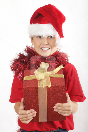 Merry Christmas stock photo, Merry Christmas - Boy wearing a santa hat and red tinsel with a red and gold gift box by Leah-Anne Thompson