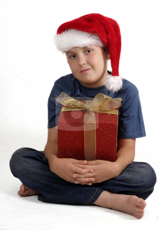 Sitting boy with Christmas Gift stock photo, Sitting cross legged boy in blue jeans and t-shirt holding a red wrapped gift with a gold bow. by Leah-Anne Thompson