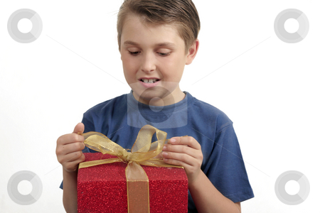 Opening a present stock photo, Young boy in t-shirt opening (or wrapping) a red and gold present by Leah-Anne Thompson