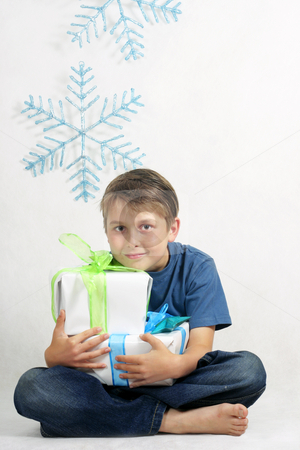 Boy holding Christmas Presents stock photo, A sitting child holding Christmas gifts tied with bright ribbon. by Leah-Anne Thompson