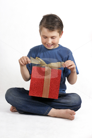 Sitting child opening a present stock photo, Sitting child in blue jeans and shirt opens up a bright red and gold present.  Suitable for christmas or birthdays. by Leah-Anne Thompson
