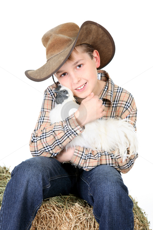 Farm boy holding a chicken stock photo, Boy sitting on a lucerne bale and holding a bantam chicken by Leah-Anne Thompson