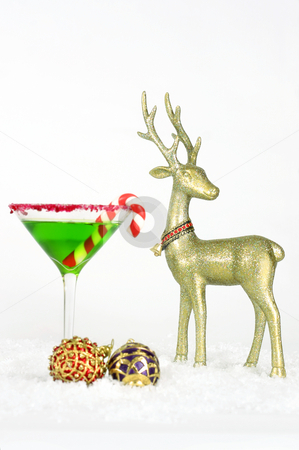 Christmastime stock photo, A christmas drink, with red and purple baubles and golden reindeer decorations on snow.