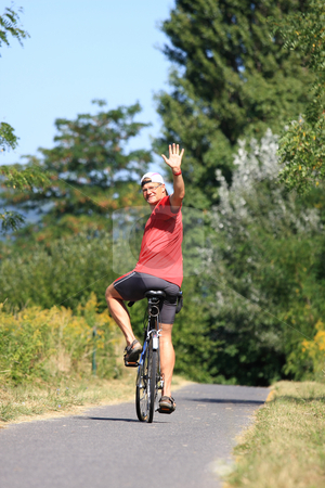 Biker stock photo, A young man is waving from the bike cheerfully by ARPAD RADOCZY
