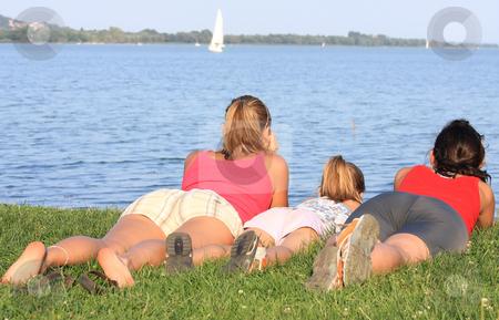 Family stock photo, Three joyful girls are lying prone on the shore by ARPAD RADOCZY