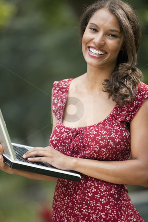 Young Woman Using Laptop stock photo, Young woman using laptop in outdoor setting. Vertically framed shot. by Edward Bock