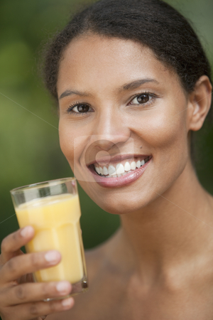 Young Woman Drinking Orange Juice stock photo, Closeup of young woman drinking orange juice in outdoor setting. Vertically framed shot. by Edward Bock